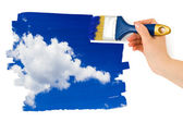 Hand with paintbrush painting sky — Stock Photo
