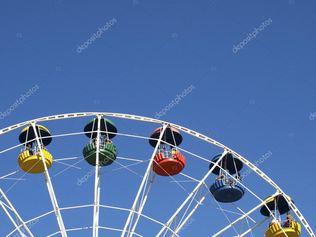 Ferris wheel color cabins against blue sky. —Photo by tuulijumala