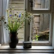 Field flowers in a jug at a window - Stock Photo