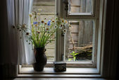 Field flowers in a jug at a window — Stock Photo