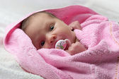 Infant baby in pink towel — Stock Photo