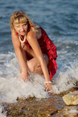 Woman in red dress in sea sparks — Stock Photo