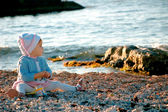 A baby sitting near the sea — Foto Stock