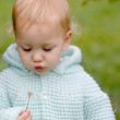 Baby glowing into dandelion — Stock Photo