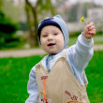 Baby boy giving dandelion — Stock Photo