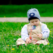 Baby boy sitting amoung flowers — Stock Photo