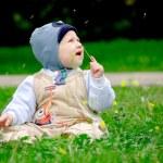 Baby boy sitting among dandelions — Stock Photo