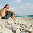 Young man sitting on the beach - Stock Photo