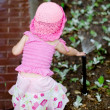 A child playing with sprinkler (back) — Stock Photo