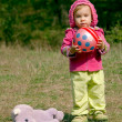 Little girl with a ball and a hippopotam - Stock Photo