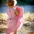 Kid girl lifting up her dress — Stock Photo #1222911