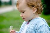 Sweet baby holding dandelion — Stock Photo
