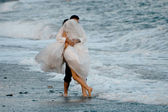 Bride and groom on the beach — Stok fotoğraf
