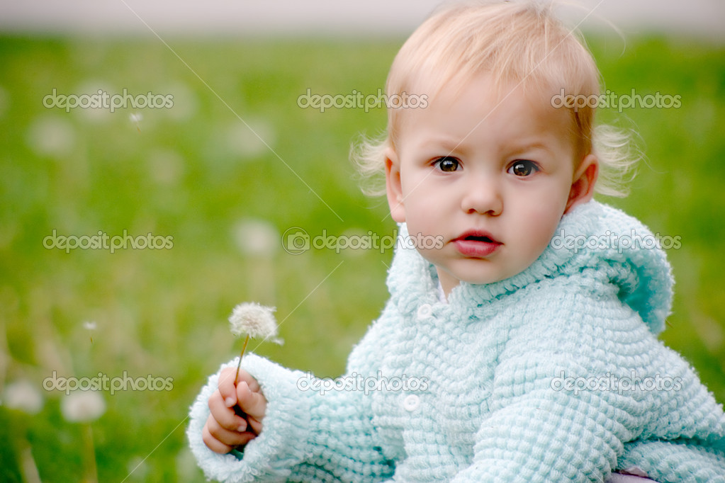 Small child holding a dndelion and sitting on the grass — Stock Photo #1220453