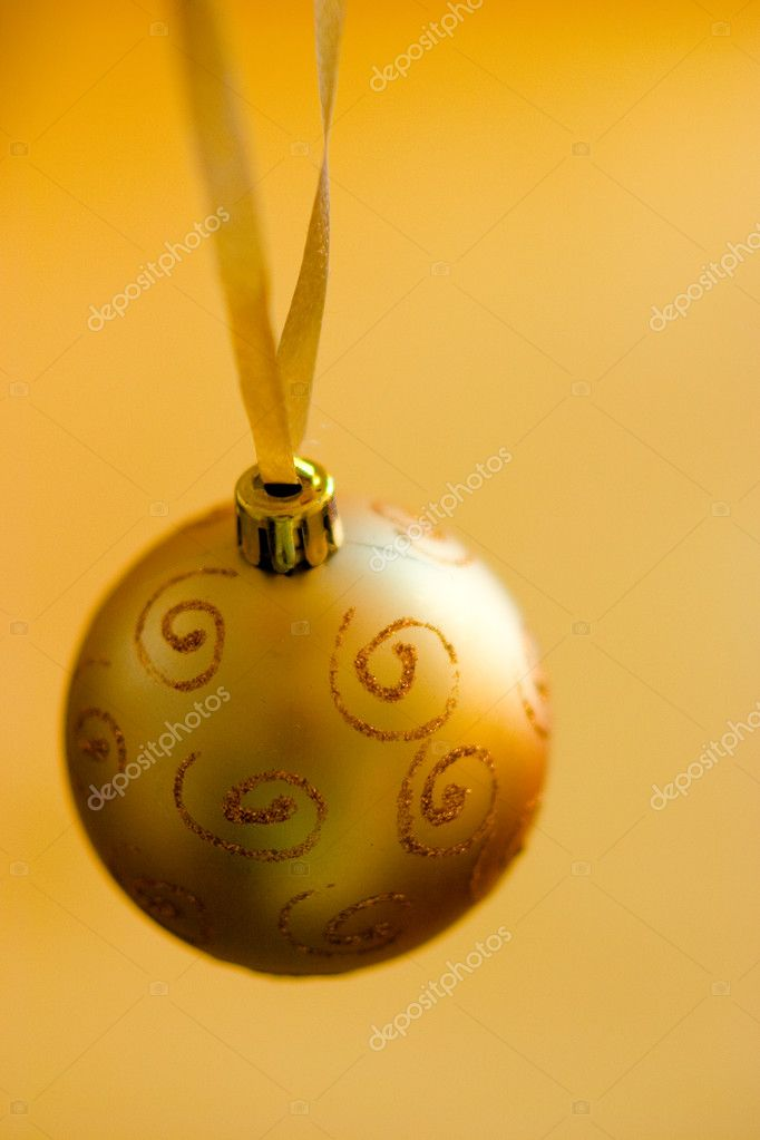 A gold christmas ball on yellow background — Stock Photo #1220692