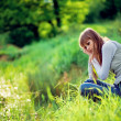 Girl sitting near lake in grass — Stock Photo