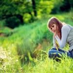 Girl sitting near lake in grass — Stock Photo