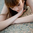 Stock Photo: Womlying on asphalt