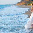 Bride running away from sea waves — Stockfoto