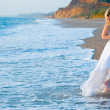 Bride running away from sea waves - Stock Photo