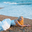 Bride lying at sea coast — Stockfoto