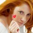 Sexy girl with red hair holding a heart — Stock Photo