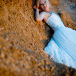 Bride lying on rock - Stock Photo