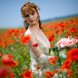 Girl sitting among poppies — Stock Photo #1246086