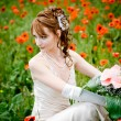 Stock Photo: Girl sitting among poppies
