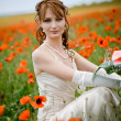 Girl sitting among poppies — Stock Photo