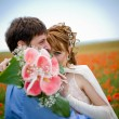 Young couple in poppy field — Stock Photo