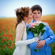 Young couple in poppy field — Stock Photo #1246129