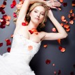Bride lying among rose petals — Photo