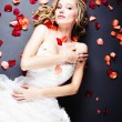Bride lying among rose petals - Stock Photo