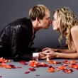 Wedding couple among rose petals — Stock Photo