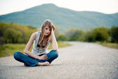 Teenager girl sitting on road — Stock Photo