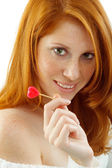 Sexy woman with red hair holding a heart — Stock Photo