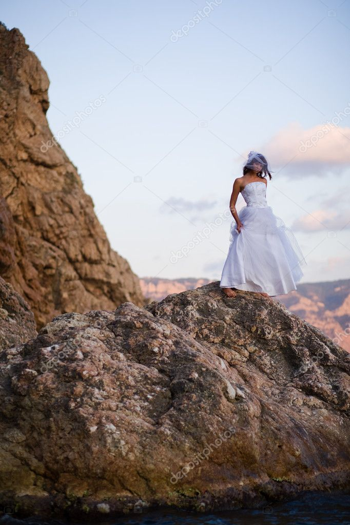 Bride in fashion wedding dress posing on mountain over sea — Stock Photo #1241044