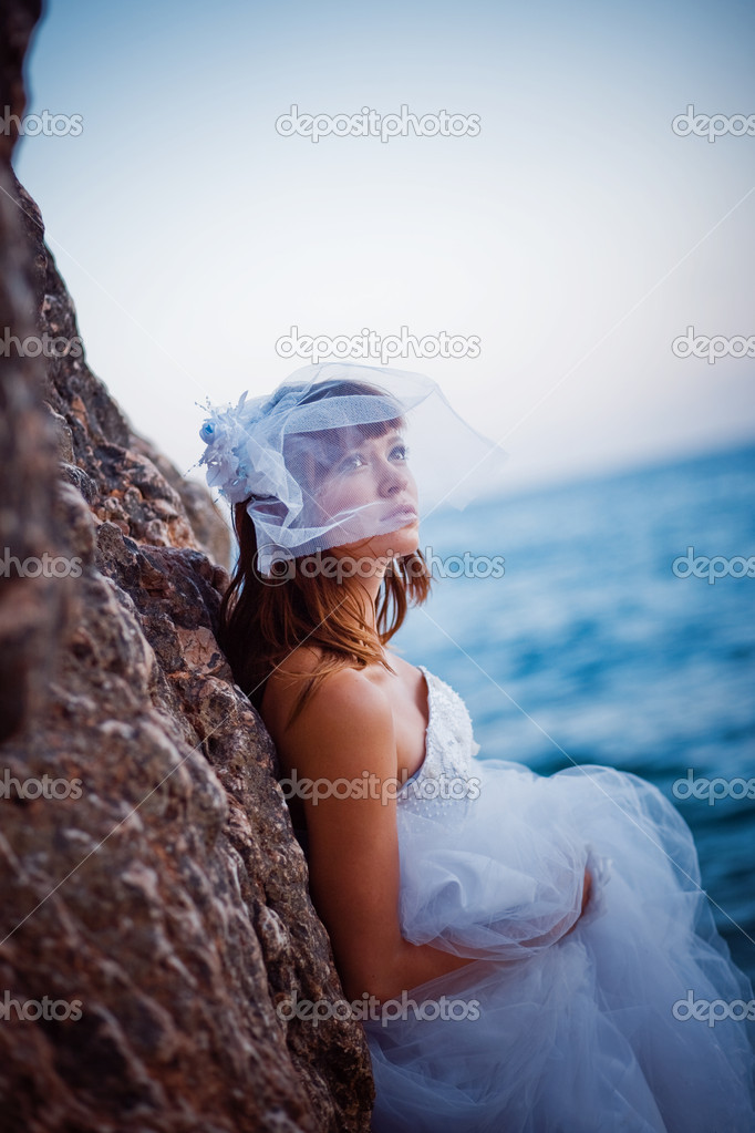 Portrait of bride in wedding dress staying near rock at sea backdrop — Stock Photo #1241150
