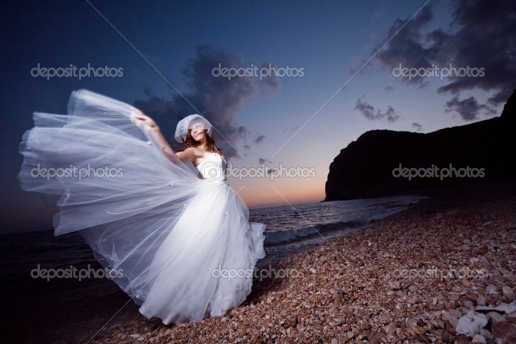Bride posing showing her wedding dress on sunset beach — Lizenzfreies Foto #1241606