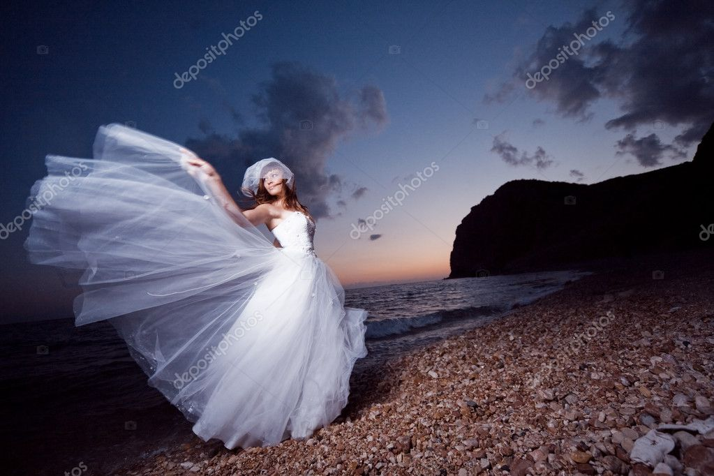 Bride posing showing her wedding dress on sunset beach — Stok fotoğraf #1241606