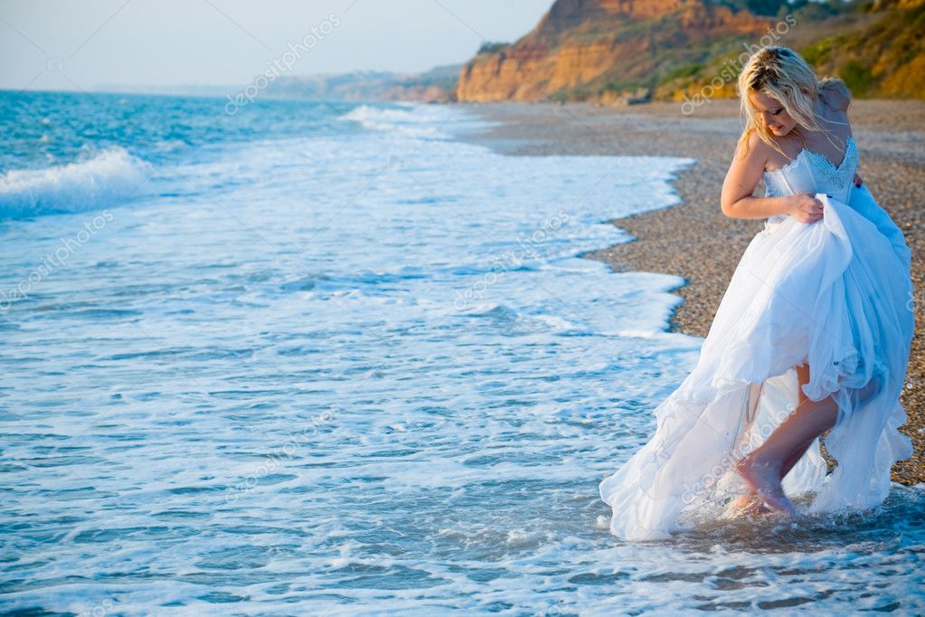 Bride wearing wedding dress running away from sea waves at coastline — Stock Photo #1244177