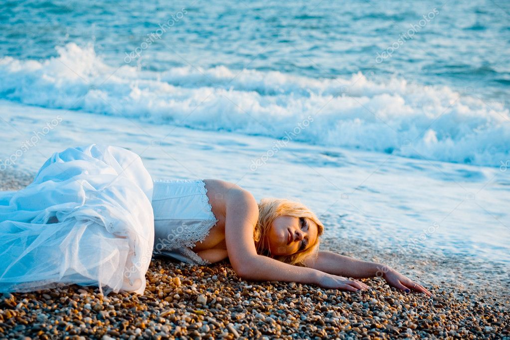 Trash the wedding dress series. Tired bride lying on ocean coast near sea waves. — Foto de Stock   #1244226