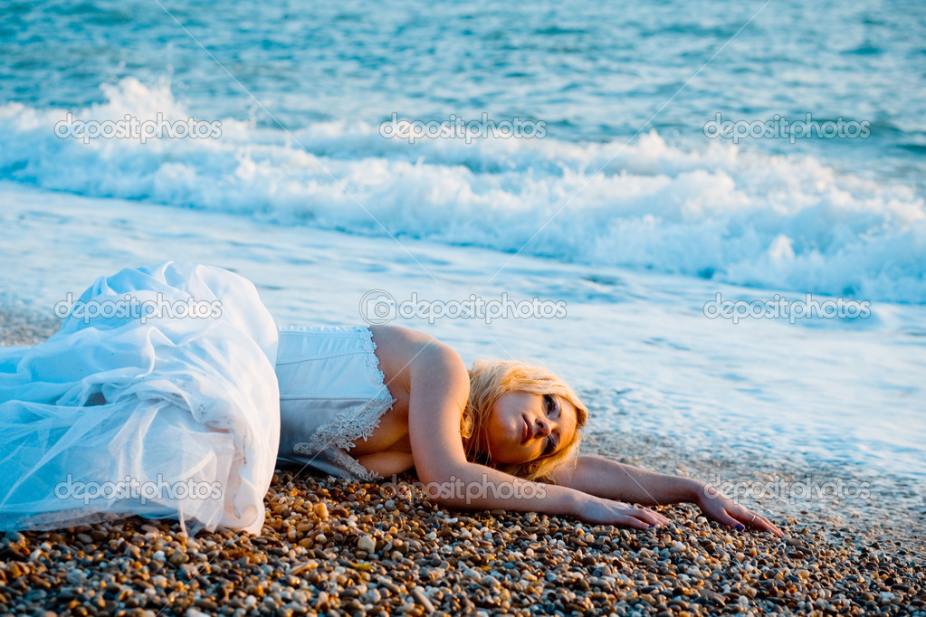 Trash the wedding dress series. Tired bride lying on ocean coast near sea waves. — Foto Stock #1244226