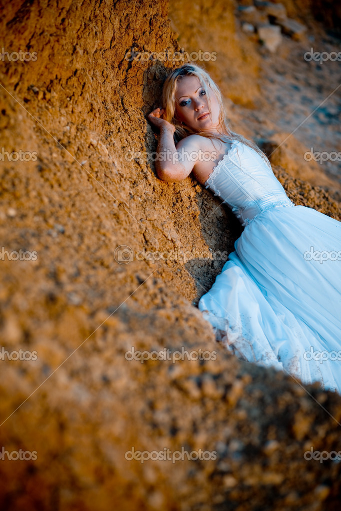 Trash the wedding dress series. Tired bride near sandy rock. — Stock Photo #1244402