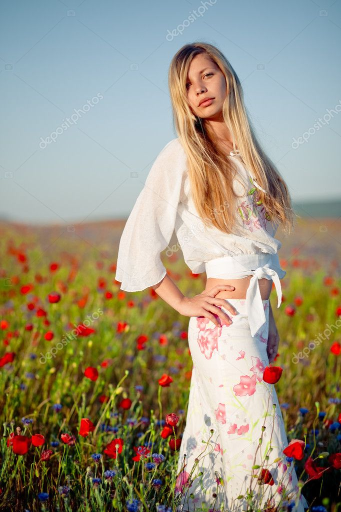 Nice blond woman with long hair staying in field of flowers  Stock Photo #1245974