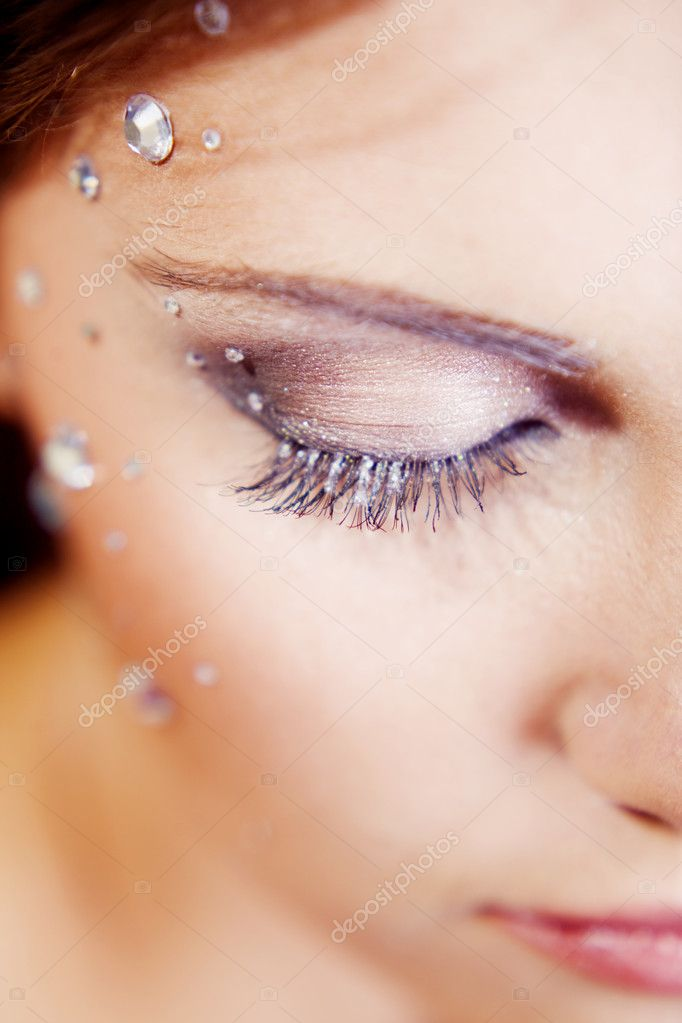 Beautiful half face with make-up and sparkles. Shallow DOF, focus on the eye.  Stock Photo #1246051