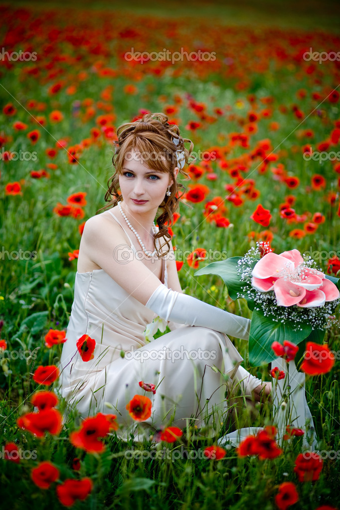 Bride sitting among fields of poppies — Stock Photo #1246105