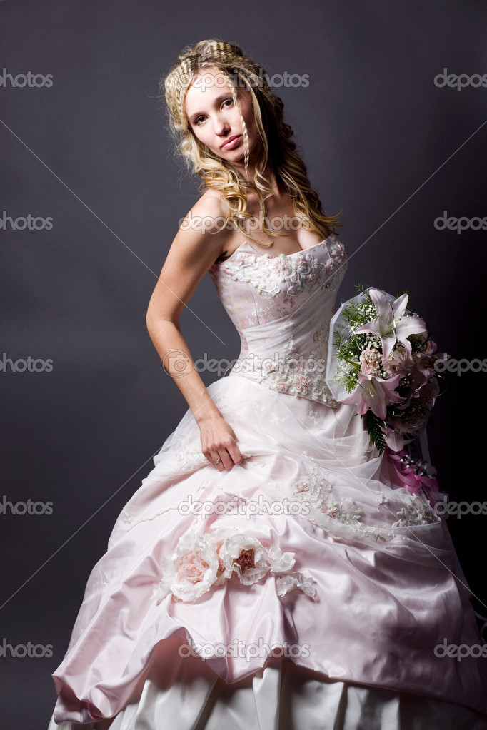 Beautiful blond bride wearing wedding dress posing on gray studio background — Photo #1246760
