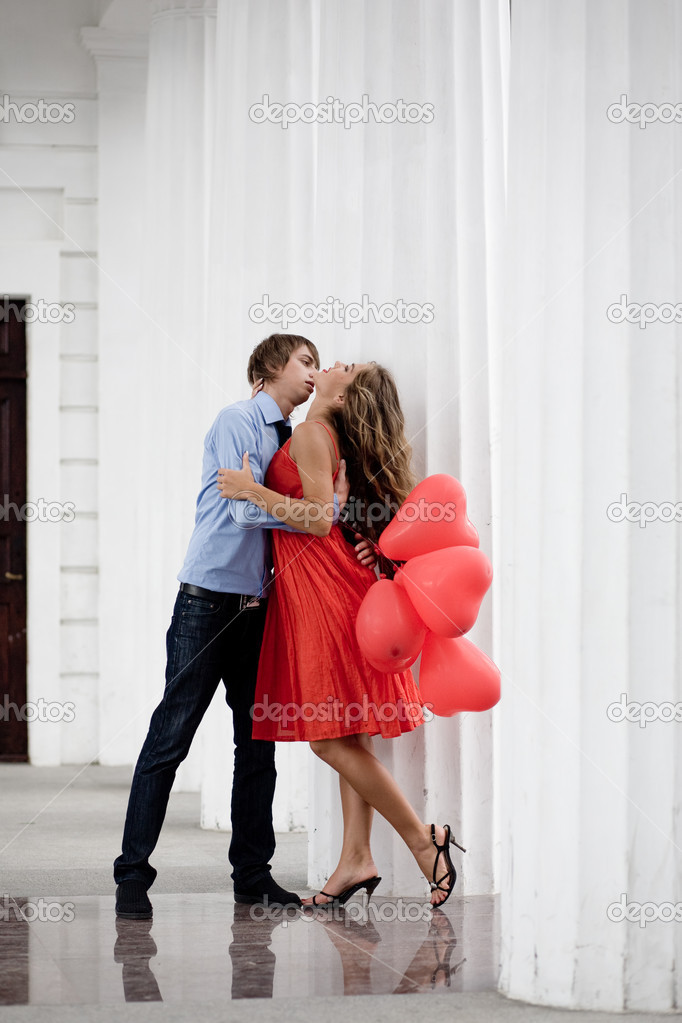 Young couple kissing among white columns and holding bunch of baloons-hearts  Stock Photo #1246892